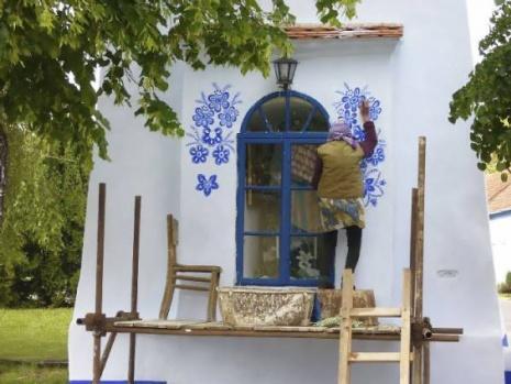 """Eski bir tarım işçisi olan Agnes, yıllardır boyama işiyle uğraşan köyündeki diğer kadınlar sayesinde bu hobiyi edinmiş. Mavinin capcanlı bir tonu ve küçük bir fırçayla geleneksel Moravya* işçiliğinden esinlenen Agnes, internette ve yerel çapta övgü kazansa da bunu sadece zevk için yaptığını söylüyor: """"Ben bir sanatçıyım. Resim yapmaktan zevk alıyorum ve olabildiğince en iyi şekilde yardım etmek istiyorum""""."""