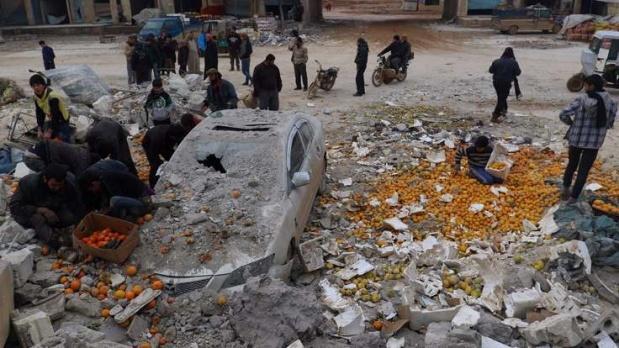 Reuters, 2017'nin çarpıcı fotoğraflarını derledi.   İlk görselde, 14 Ocak günü Suriye'nin İdlib kentinde yaşanan bir hava saldırısının ardından ortalığa saçılan portakaları toplayan insanlar görülüyor.